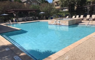 Finest Finish Blends Texas - Blue Star white swimming pool with spa in the distance
