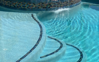 Universal Mini Pebble Laguna Blue rounded pool steps with tiled spa in background