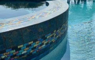 Universal Mini Pebble Laguna Blue spa side with iiridescent tile