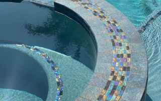 Universal Mini Pebble Laguna Blue spa with iridescent tile detail