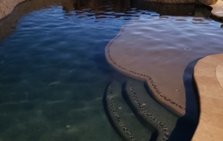 Universal Mini Pebble Midnight and Sandy Beach rounded pool with steps and spa in background