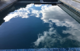 Universal Mini Pebble Midnight pool with blue tile sky reflection