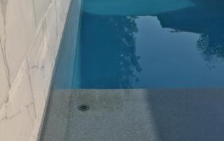 Universal Mini Pebble Tahoe + Lakeside Sparkle quartz pool with baja shelf close up