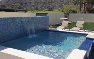 Finest Finish pool with water feature and tile wall - Universal Mini Pebble Laguna White - with mountain and golf course background